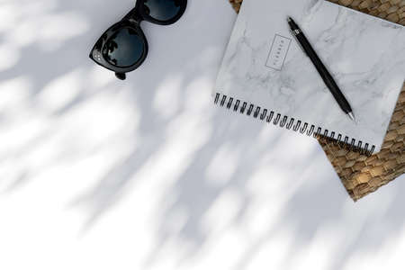 Trendy sunglasses, planner with palm leaf shadow on white background
