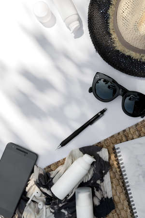 Trendy sunglasses, planner, hat and cosmetic cream with palm leaf shadow