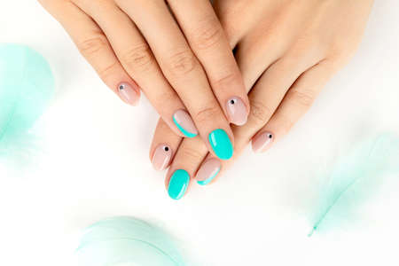 Well-groomed female hands with a bright modern design on white background. Beauty self care concept