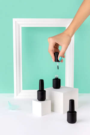 Bottle of nail varnish on podium with womans hand on turquoise background. Beauty salon product mock up template in minimal slyle.