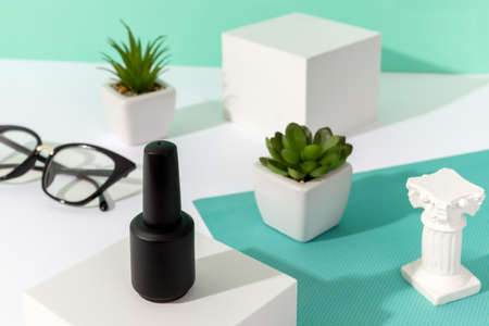 Bottle of nail varnish on podium with house plants on turquoise background. Beauty salon product mock up template in minimal slyle.