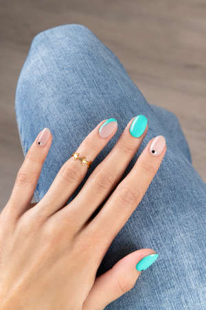 Manicured womans hand with fashionable golden ring. Beauty fashion concept 免版税图像