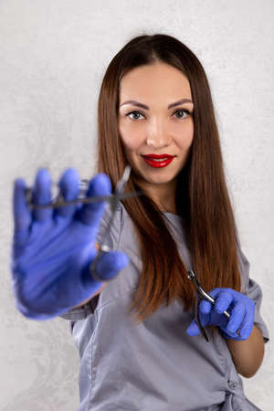 Young adult woman in rubber gloves holds manicure tools