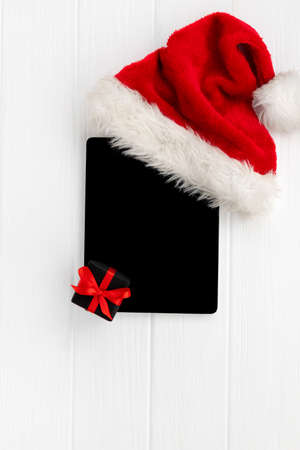 Digital tablet with Santa hat and gift on white wooden background