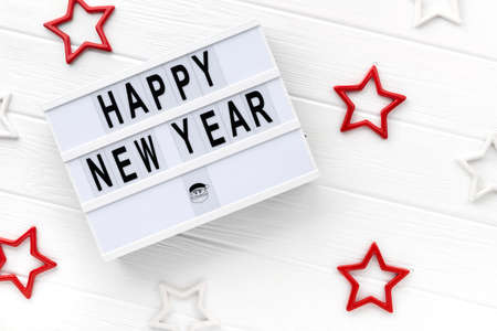 Light box with text Happy New Year on white wooden background