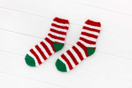 Striped socks with laptop on white wooden background