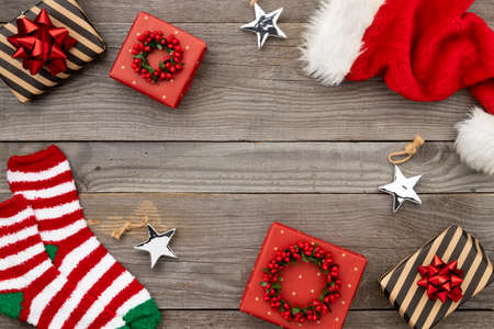 Red Santa hat, gift boxes and socks on old wooden background