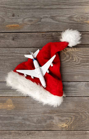 Red Santa hat with toy plane on old wooden background 免版税图像