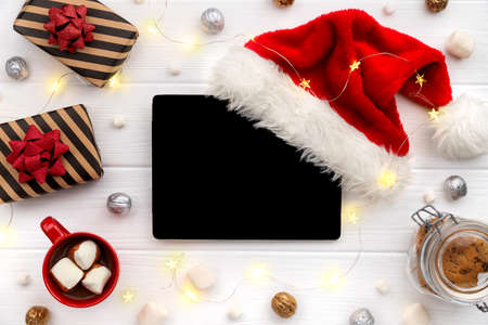 Digital tablet with hot chocolate and gifts on white wooden background 免版税图像