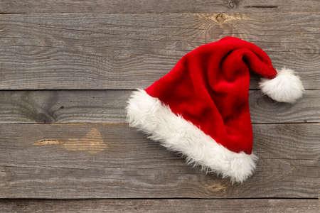 Red Santa hat on old wooden background 免版税图像