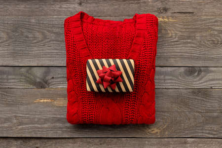 Red knitted sweater with a gift on old wooden background