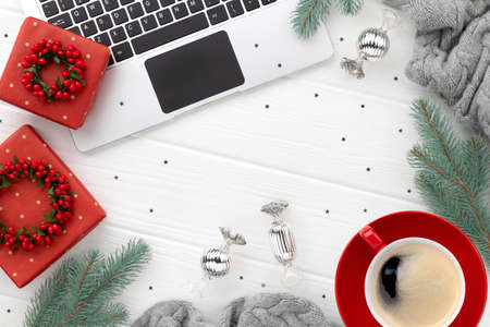 Laptop with coffee and gifts on white wooden background