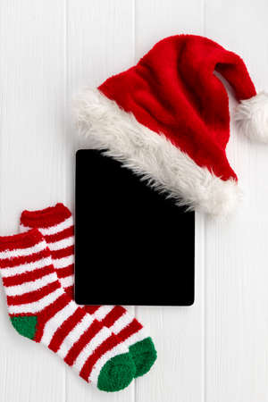 Digital tablet with Santa hat and socks on white wooden background 免版税图像