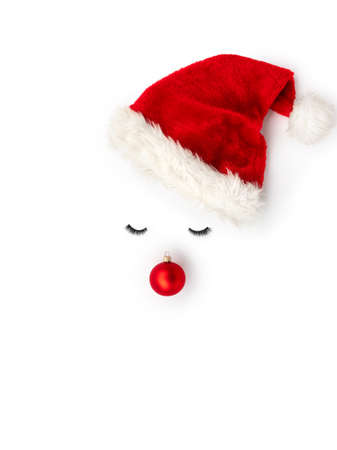 Snow man concept made of hat, red bauble decoration and eyelashes