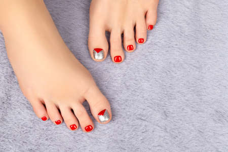 Beautiful female legs with Christmas nail design on gray fluffy background. Manicure pedicure beauty salon concept.