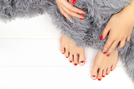 Beautiful womans legs and hands with fluffy blanket. Manicure pedicure beauty salon concept.