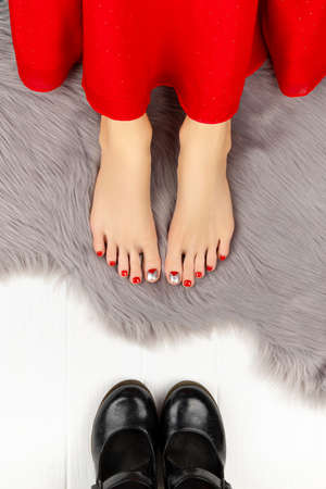 Female legs with red nails and shoes on gray fluffy blanket. Christmas celebration concept.