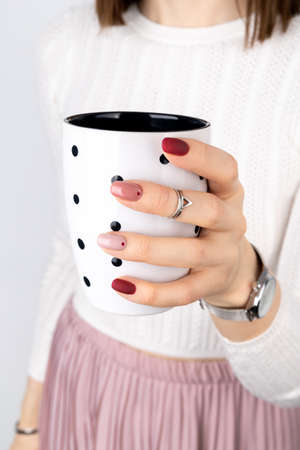 Woman with a pink manicure in minimal style holding a cup of coffee or tea
