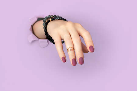 Womans hand with purple matte manicure through hole in paper background. Fashionable spring summer nail design.