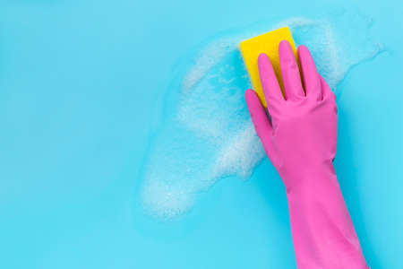 Womans hand in pink rubber glove wash by sponge on blue background