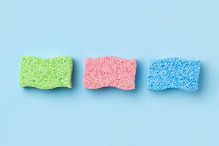 Creative layout with sponges for dishwashing on blue background. 免版税图像