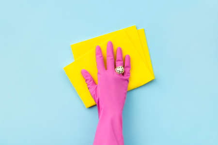 Womans hand in pink rubber glove wipe by rag on blue background