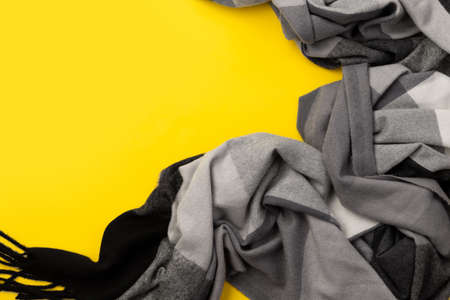 Top view flat lay gray trendy scarf on yellow background 免版税图像
