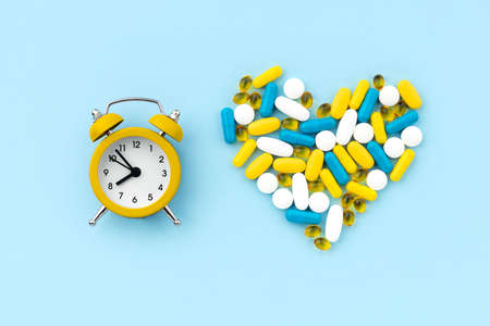 Medical pills in heart shape with alarm clock on blue background
