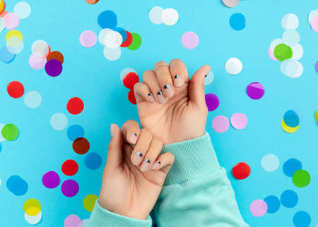 Woman's hands with colorful confetti on blue