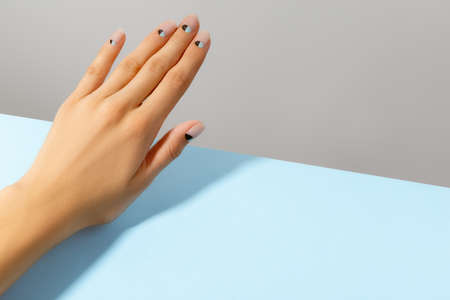 Beautiful groomed woman's hand with nude and blue matte nail design