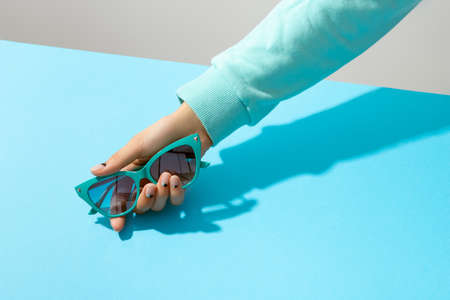 A Woman's hand holding sunglasses on blue