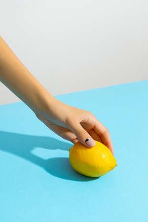 Woman's hand holding lemon on blue