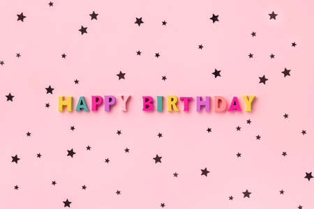 Happy birthday inscription from wooden colorful letters with confetti