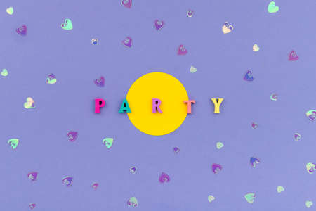 Word party from wooden colorful letters on violet background 免版税图像