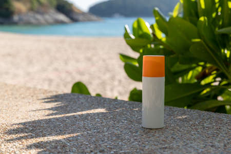 Bottle of sunscreen lotion on the beach by the sea 免版税图像