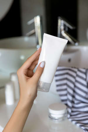 Womans hand holding cleansing foam in the bathroom