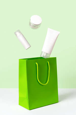 Creative layout with levitating beauty products and paper bag on green