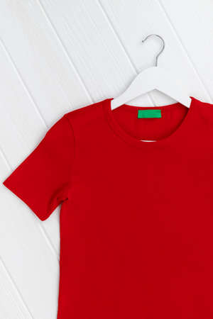 Flat lay top view womens t-shirt on hanger on white background