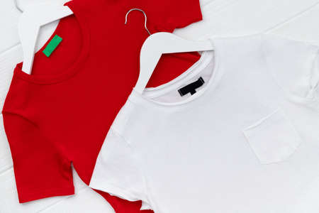 Flat lay top view womens t-shirts on hanger on white background 免版税图像