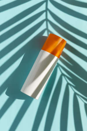 Bottle of sunscreen with palm leaf shadow on blue background