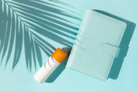 Bottle of sunscreen and notepad with palm leaf shadow on blue background