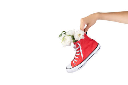 Womans hand holding trendy red sneaker with flowers