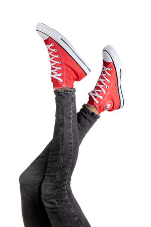 Legs of a young woman in stylish red sneakers on white background.