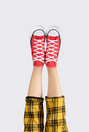 Legs of a young woman in stylish red sneakers on gray background. 免版税图像