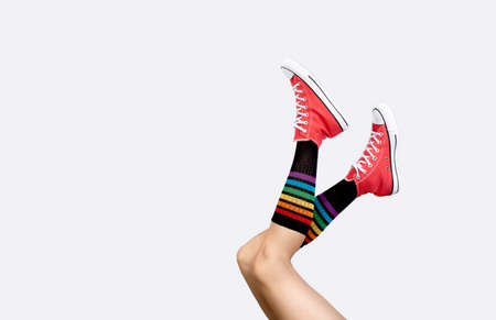 Womens legs in stylish red sneakers and rainbow socks on gray background 免版税图像