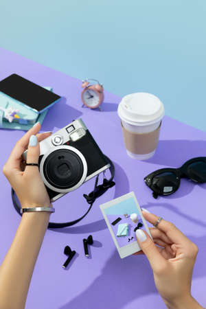Womans hands holding instant camera and shot. Female summer accessories 免版税图像