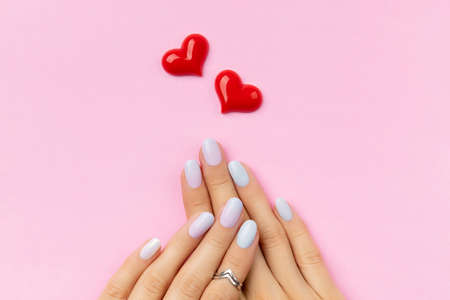 Womans hands with trendy manicure on pink background. Summer nail design
