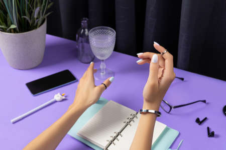 Beautiful groomed womans hands over violet table. Female summer accessories