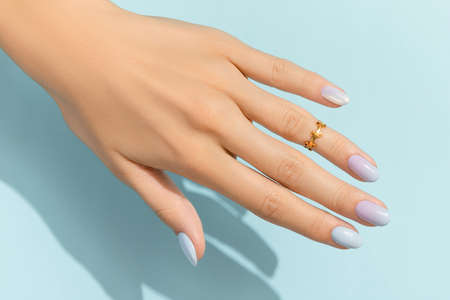 Womans hands with trendy manicure on blue background. Summer nail design