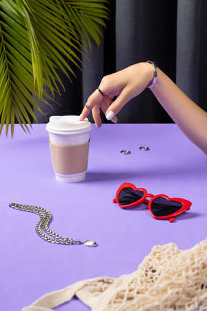 Beautiful groomed womans hand with paper coffee cup. Female summer accessories 免版税图像